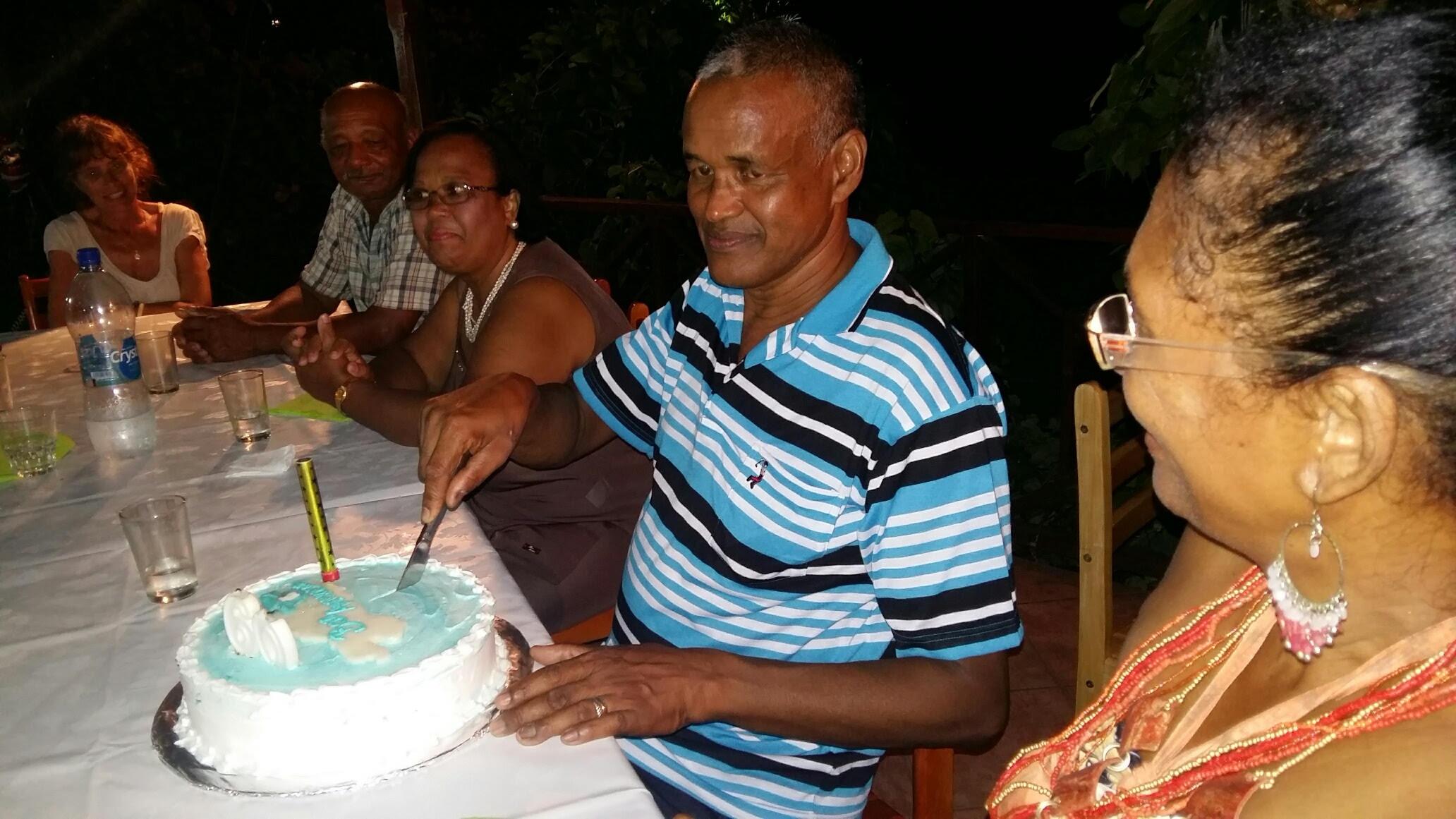 Jean Bundhoo coupant son gâteau d'anniversaire